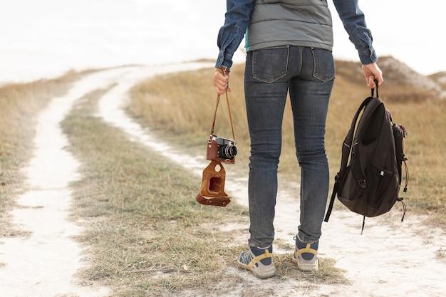 Вид сзади путешественник держит рюкзак