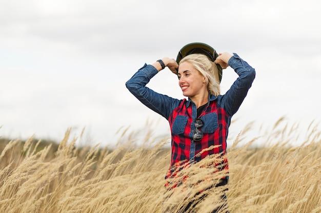 Красивая женщина в окружении пшеницы позирует