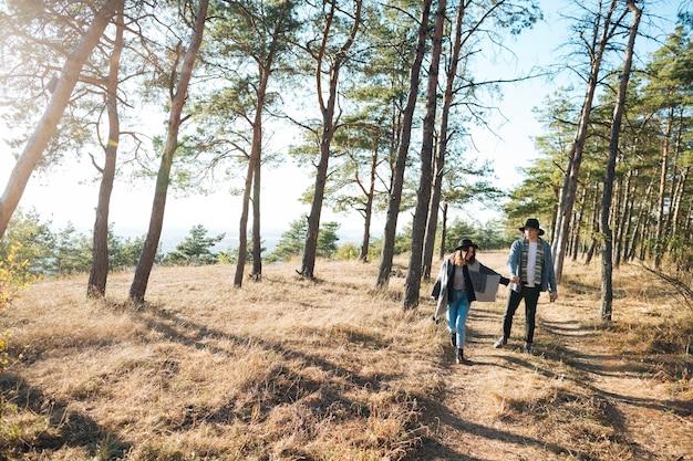 公園を歩いているロングショットカップル