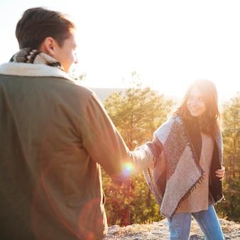 手を繋いでいるかわいい若いカップル