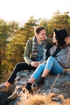 屋外の岩の上に座っている若いカップル