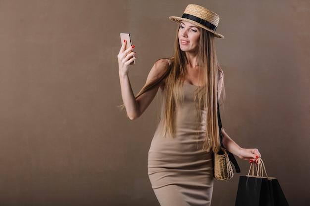 彼女の携帯電話をチェックする見事な女性の正面図