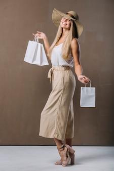 買い物袋を保持しているかなり若い女性