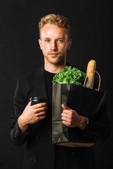 Вид спереди красивый мужчина держит продукты