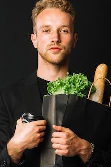 食料品の袋を保持しているハンサムな男