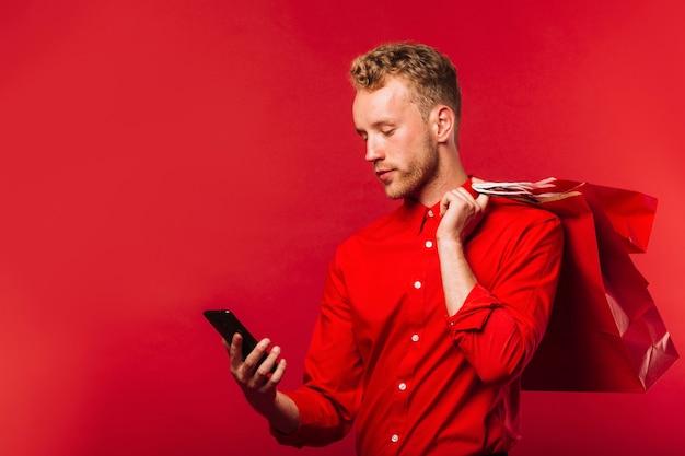 Вид спереди молодой человек, проверка его телефон