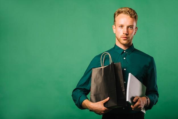 買い物袋を持つ正面若い男
