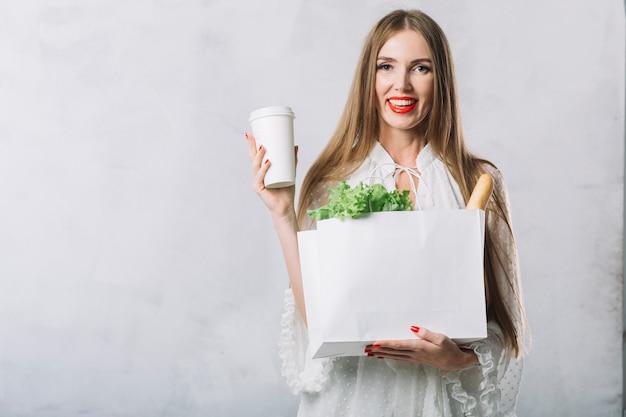 Вид спереди женщина с продуктами улыбается