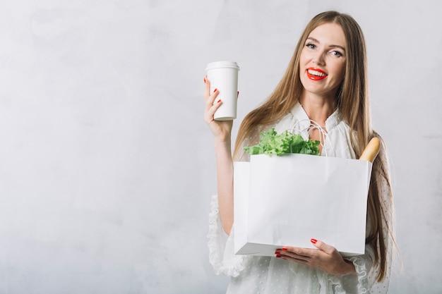 食料品の袋を保持している美しい若い女性