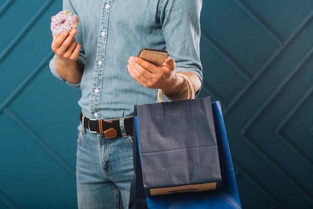 Взрослый мужчина крупного плана держа хозяйственные сумки