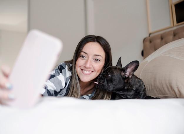 Смайлик молодая девушка, принимая селфи со своей собакой