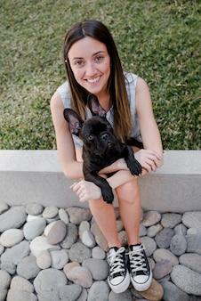 彼女の子犬を保持している高角度の女の子