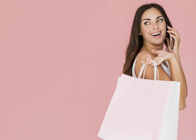 Милая женщина с хозяйственными сумками, оглядываясь назад