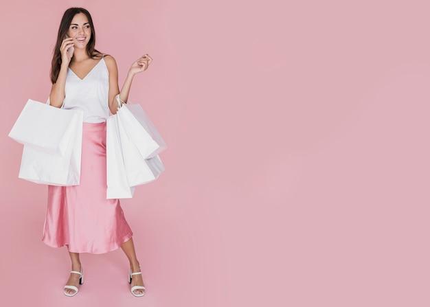 Красивая девушка с множеством сумок на розовом фоне