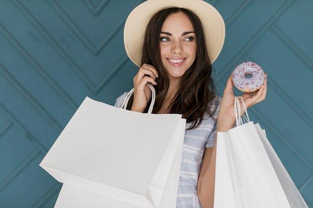 帽子とドーナツを持つ陽気な若い女性
