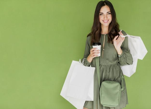 緑のハンドバッグと緑の背景にコーヒーを持つ女性