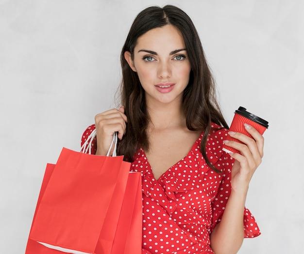 赤いショッピングバッグとコーヒーを持つ女性