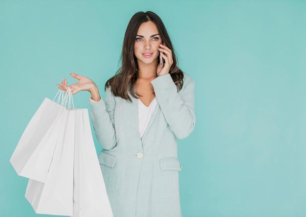 電話で話している買い物袋を持つ女性