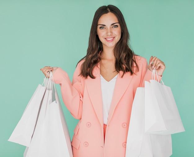 カメラに笑顔ピンクのジャケットの若い女性