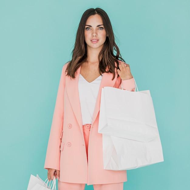 カメラ目線ピンクのスーツのブルネットの女性