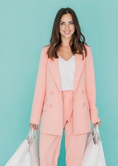 青色の背景にピンクのスーツの女性