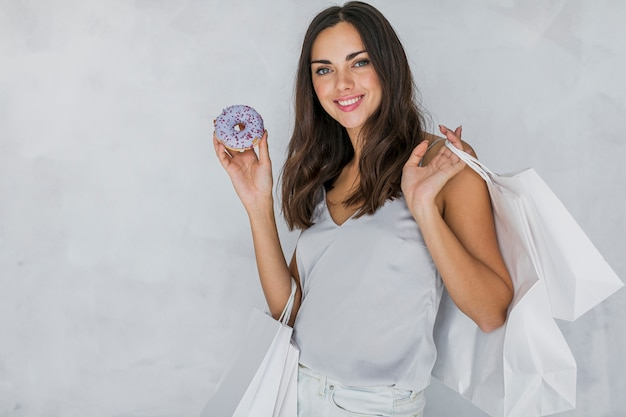 ドーナツとショッピングネットのブルネットの女性