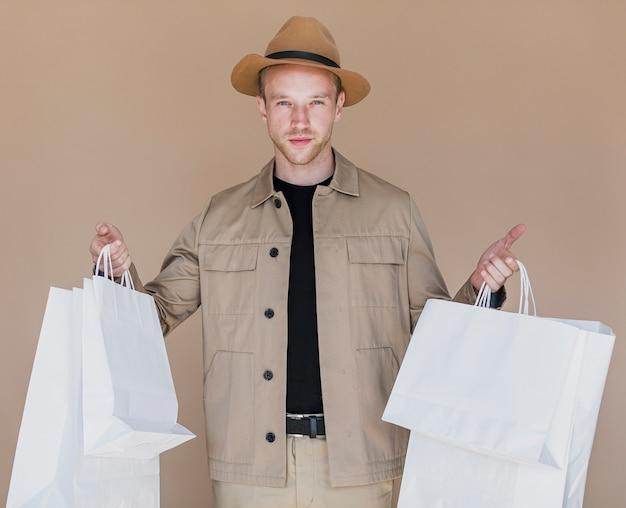 両方の手で買い物袋を持つ若い男