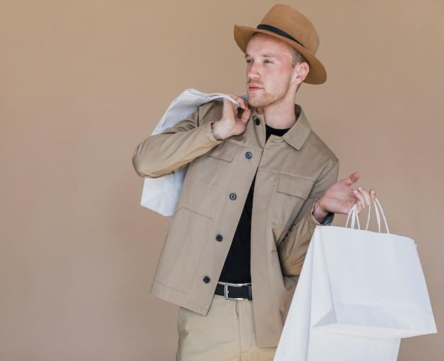頭とショッピングネットの帽子と若い男