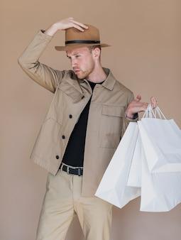 頭と買い物袋に帽子を持つ男