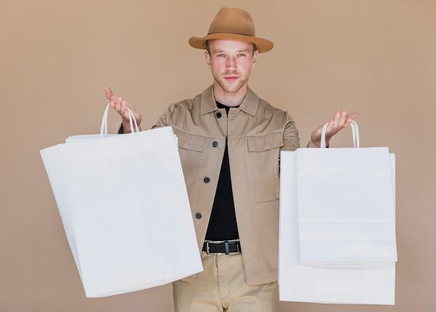 ショッピングネットを保持している帽子の若い男