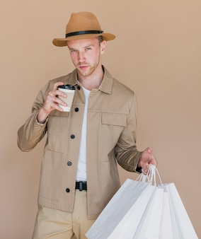 白い買い物袋とコーヒーを持つ男