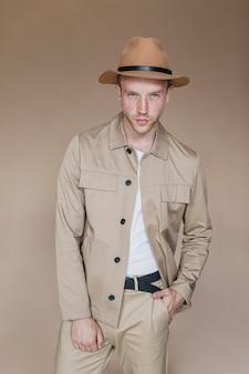茶色の背景に帽子を持つ金髪の男