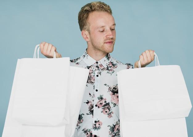 青色の背景に買い物袋を持つ金髪の男