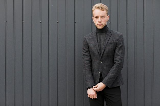若い男が彼のジャケットの袖をアレンジ