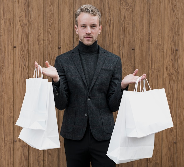 両方の手で買い物袋を持つスタイリッシュな男