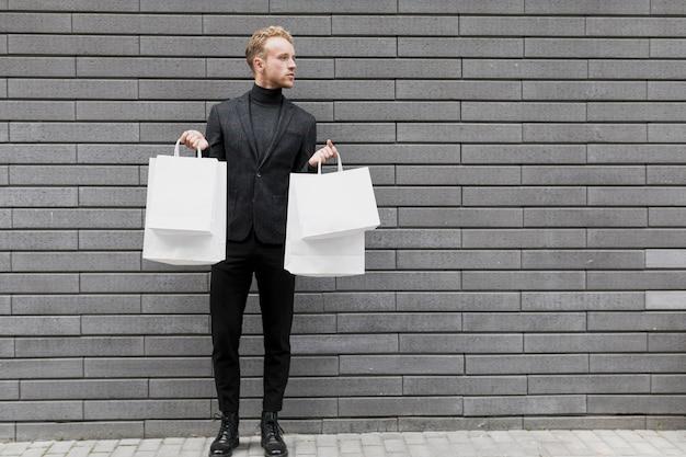 白い買い物袋を持つハンサムな男