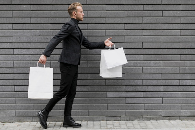 通りを歩いて買い物袋を持つ男
