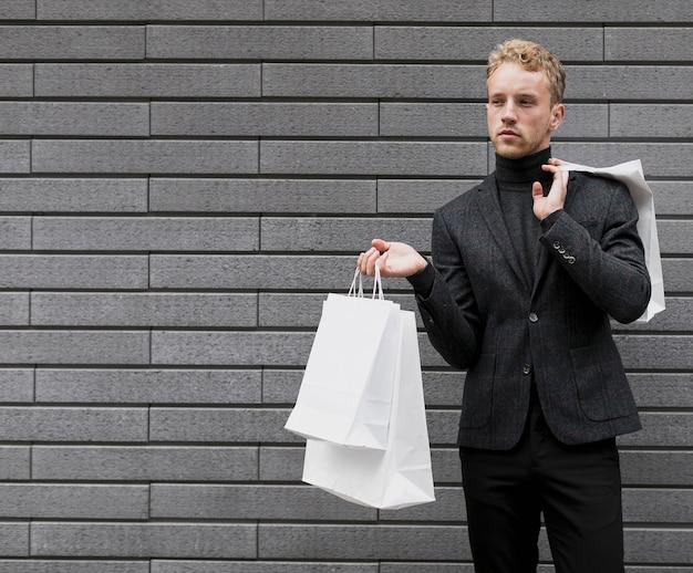 買い物袋を持つ孤独な若い男