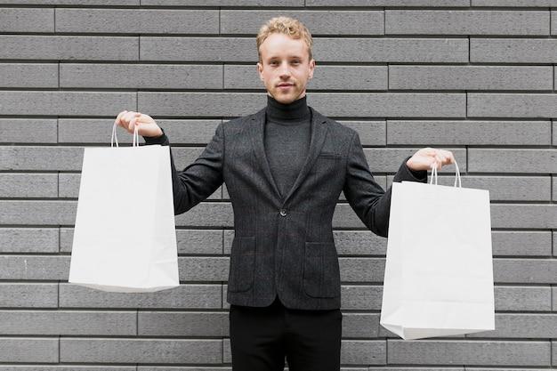 若い男が買い物袋を持ち上げる