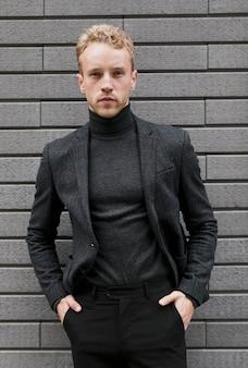 Молодой человек с руками в карманах брюк