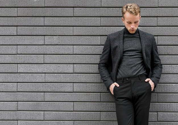 Фотогеничный молодой человек, прислонившись к стене