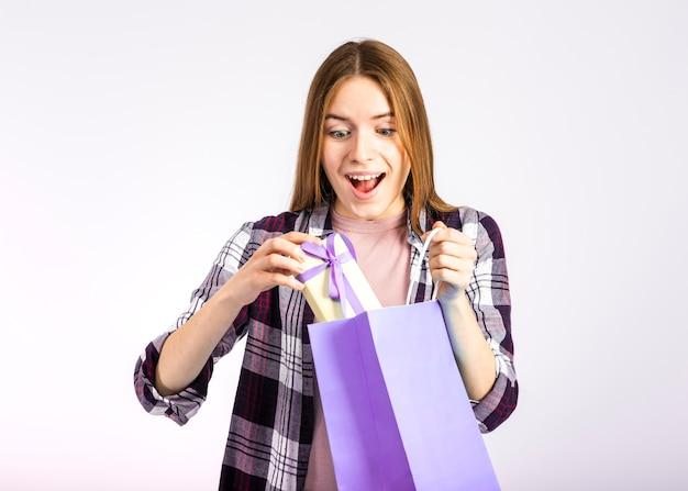 バッグから贈り物を取ってミッドショット女性