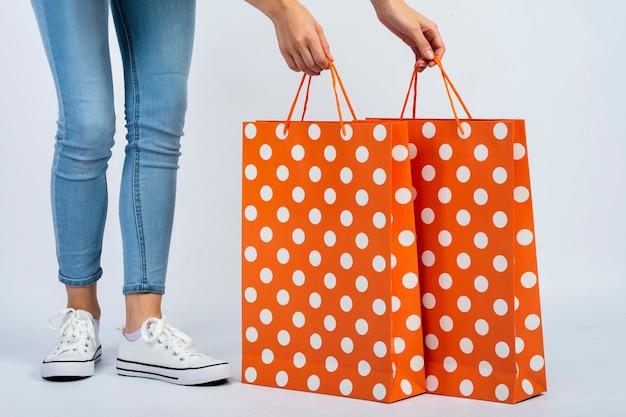 買い物袋のモックアップを足の近くに保持している女性