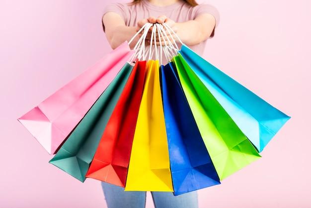 Набор красочных праздничных сумок в руках женщины