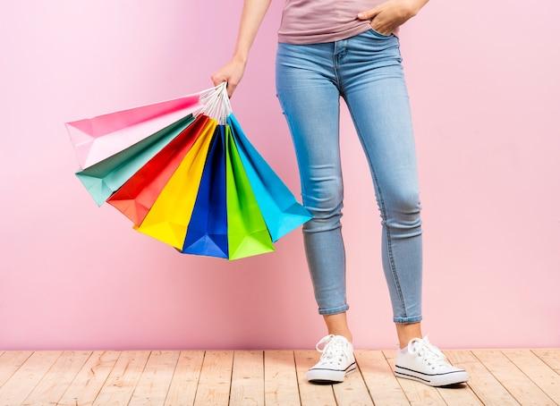 ピンクの背景を持つ梨花の手でカラフルな買い物袋