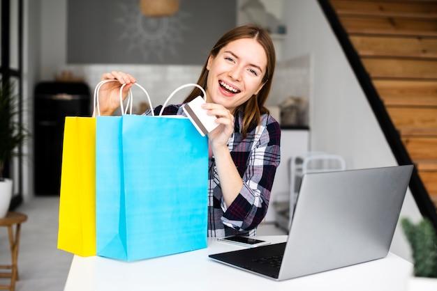 買い物袋を示す若い笑顔の女性