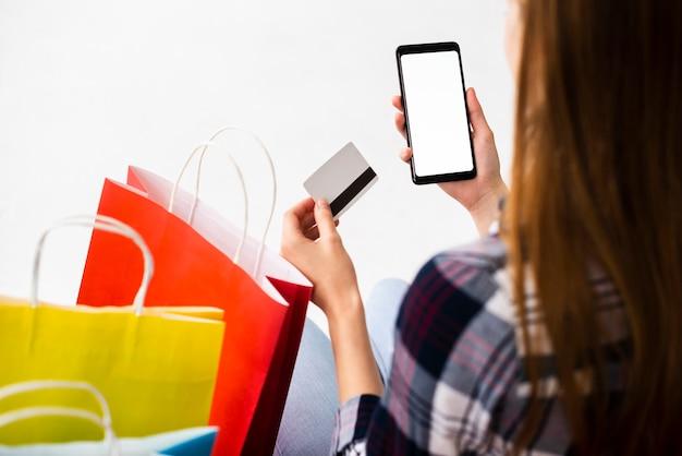 Вид сзади женщина ищет, проверяя телефон макет