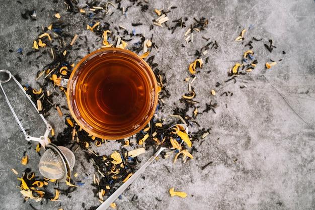 大理石の背景に注入器とお茶のフラットレイアウトカップ