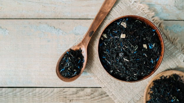 木製の背景上にボウルでおいしいお茶のハーブ