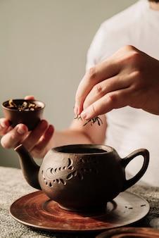 ティーポットのクローズアップでお茶のハーブを置く人